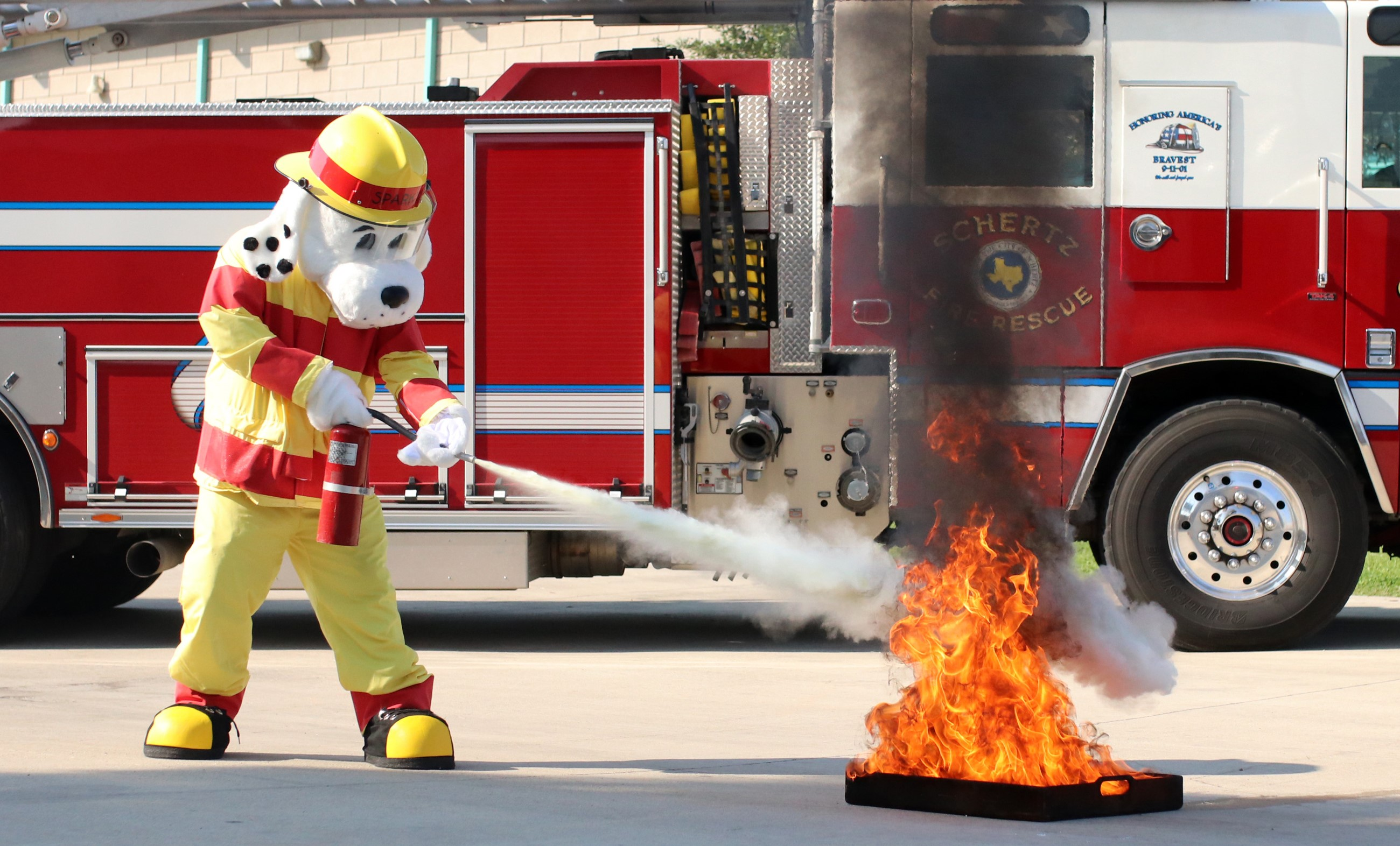Photo of Sparky extinguishing a fire using a fire extinguisher